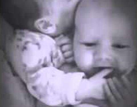 Newborn twin lends a thumb to her crying brother