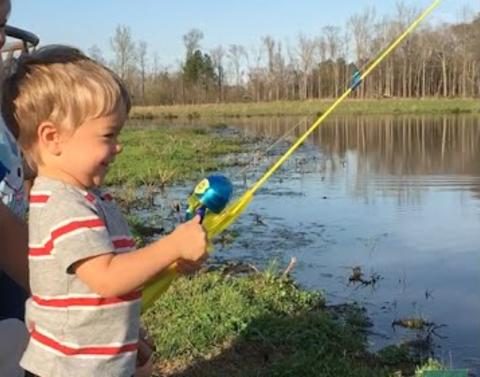 Little boy with toy fishing pole makes big catch